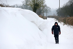 © Licensed to London News Pictures. 3/03/2018. Bodden, UK. A local man walks next to a snow drift on a blocked road at Bodden near Shepton Mallet, Somerset after a week of heavy snow. The snow has taken on the appearance of ice cream after wind has whipped up dust and mud. Photo credit: Jason Bryant/LNP
