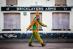 © Licensed to London News Pictures. 13/01/2018. Whittlesey UK. A reveller in costume walks around Whittlesey this morning at the 39th Whittlesey Straw Bear Festival taking place today. In times past when starvation bit deep the ploughmen of the area where drawn to towns like Whittlesey, They knocked on doors begging for food & disguised their shame by blackening their faces with soot. In Whittlesey it was the custom on the Tuesday following Plough Monday to dress one of the confraternity of the plough in straw and call him a Straw Bear. The bear was then taken around town to entertain the folk who on the previous day had subscribed to the rustics, a spread of beer, tobacco & beef. The bear was made to dance in front of houses & gifts of money, beer & food was expected.Photo credit: Andrew McCaren/LNP