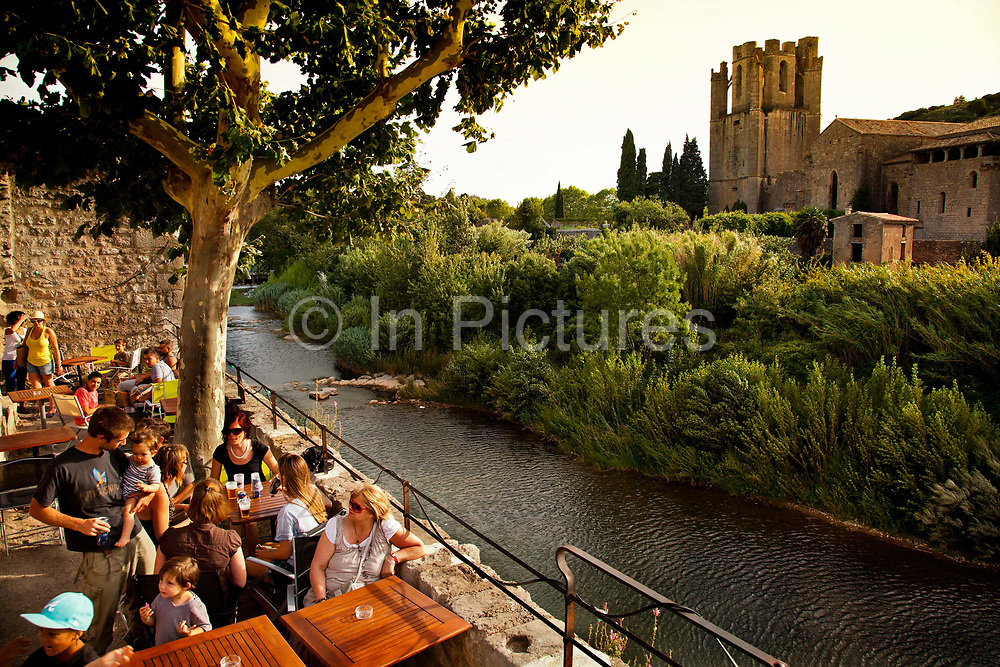 Having evening drinks in a wine bar classical medieval village by the river, 19th July 2015, Lagrasse, France.