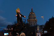 One of the organizers of the Joe Biden victory rally lifts up the Trump figure before smashing it to the ground in front of the capitol building in Denver, Colorado on 11/07/2020. People celebrate in Denver after victory of Joe Biden in the presidential election in United States. Photograph by Akash Pamarthy.