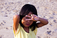 Young girl peeps through her V for victory signal.