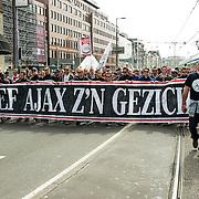 Amsterdam, 12-04-2014. Honderden Ajaxfans liepen vanmiddag een protestmars die begon bij de Stopera op het Waterlooplein en eindigde op de Dam te Amsterdam. Op deze manier toonde zij hun ongenoegen over het nieuwe Ajax-logo en vroegen zo aandacht voor de terugkeer van het oude Ajax-logo. Op de Dam voor het paleis werd een spandoek van 40 X 40 meter uitgerold met de afbeelding van het oude logo.