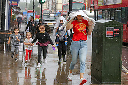 © Licensed to London News Pictures. 28/07/2021. London, UK. A woman and children are seen running for cover during a torrential downpour in north London. According to The Met Office, wet weather is expected in the capital for this week. Photo credit: Dinendra Haria/LNP