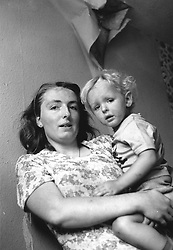 Mother holding son; damp patch with paper hanging down from ceiling behind them,