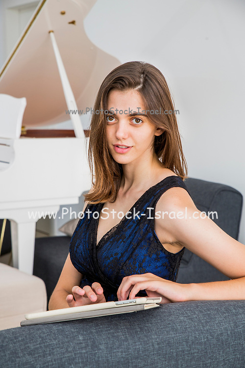 Young woman in evening dress works from home on a touchpad