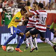 Neymar, Brazil, (left) is challenged by Steve Cherundolo and Landon Donovan, (right) USA, during the USA V Brazil International friendly soccer match at FedEx Field, Washington DC, USA. 30th May 2012. Photo Tim Clayton