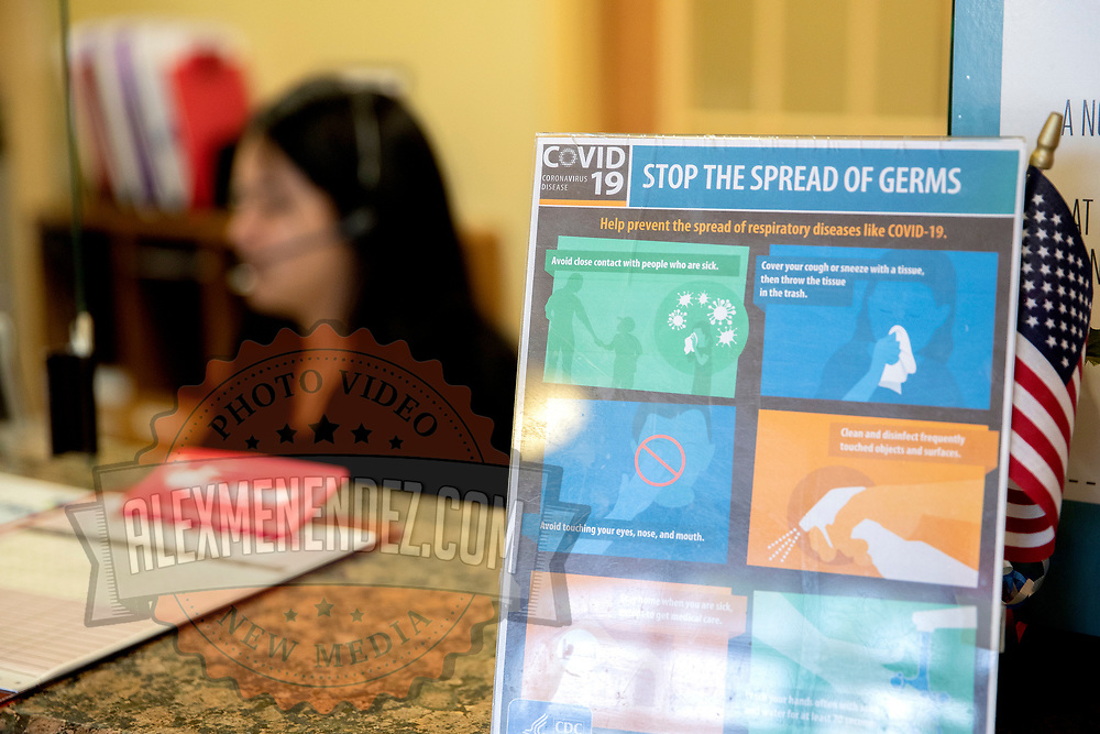 Covid-19 symptoms to be aware of are seen on a placard at the reception desk of Universal Medical Care on Tuesday, March 31, 2020 in Orlando, Florida. (Alex Menendez via AP)