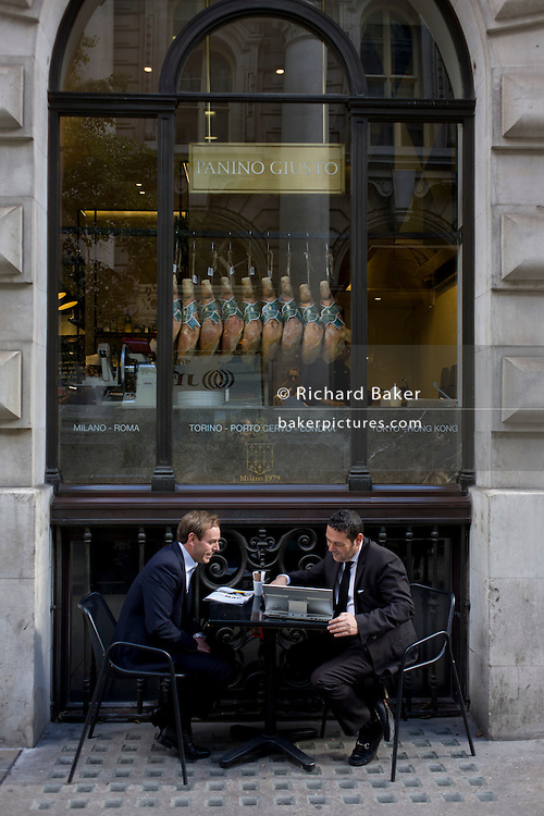 Two young businessmen sit outside a deli/cafe laughing over the contents of a laptop in the City of London.