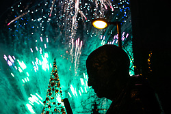 © Licensed to London News Pictures . 01/01/2020. Manchester, UK. A statue of MAHATMA GANDHI is seen against fireworks as thousands watch a fireworks display in from of Manchester Cathedral as Manchester celebrates the start of 2020 . Photo credit: Joel Goodman/LNP