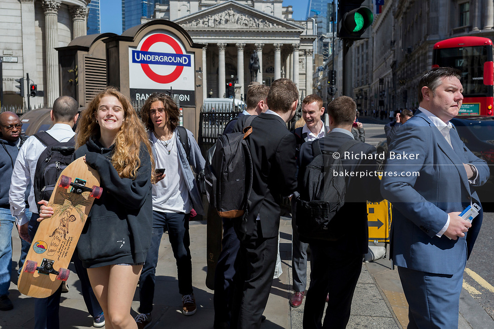 A young woman carries her upturned skateboard outside one entrance of Bank Underground Station in the City of London, the capital's ancient, financial district, on 14th May, in London, England.