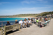 People sitting outdoors at cafe tables by the sea, Sennan Cove, Land's End, Cornwall, England, UK