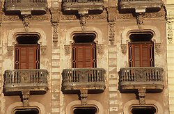 Front of building in Havana; Cuba featuring stone balconies and wooden shutters,