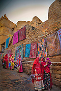 Thaditional fabrics hang for sale on the wakks of the ancient Jaisalmer Fort overlooking the Thar desert on 29th January 2018 in Jaisalmer, Rajasthan, India. The fort was built in 1156 AD by the Rajput Rawal ruler Jaisal from whom it derives its name.