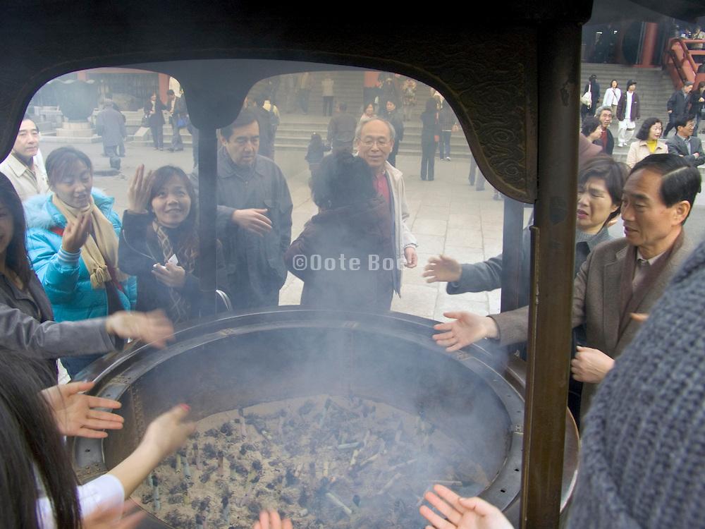people waving incense smoke over there bodies Asakusa Kannon Temple Tokyo