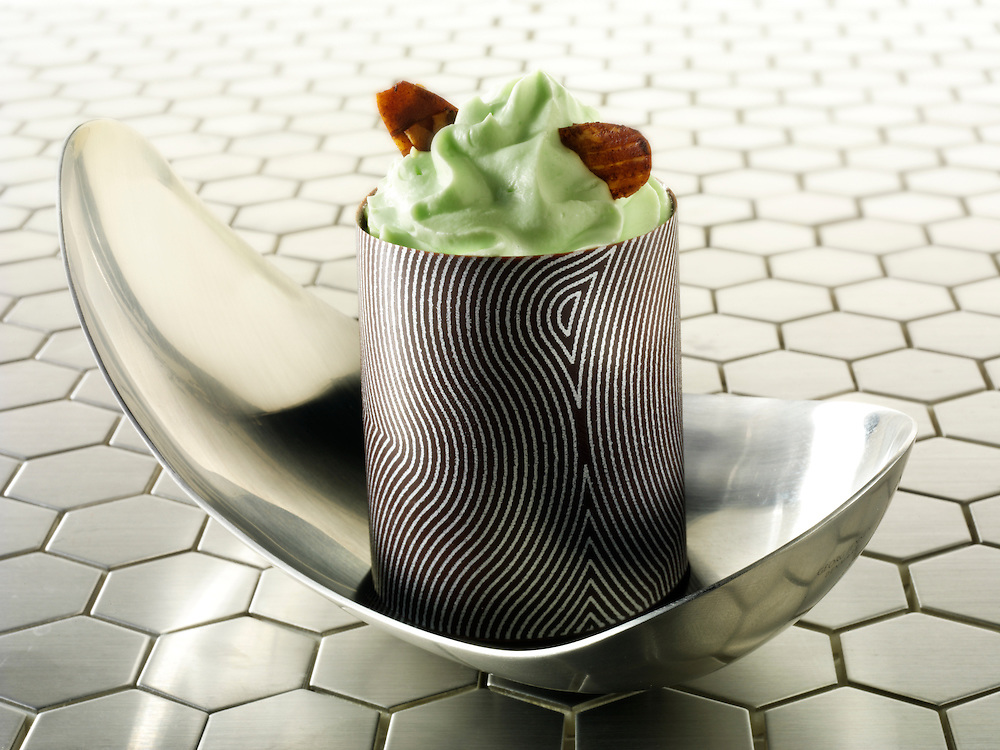 A modern Japanese cake with a pattered choclate case and mint cream, in a modern designer dish