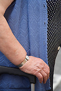 hand  and arm of an obese elderly person holding a shopping bag on wheels