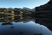 The sun begins to set behind the mountains of the Picos de Europa at Lago de la Ercina