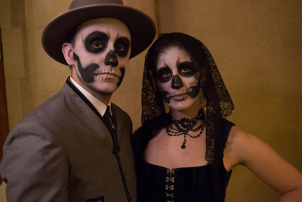 A couple with skull-themed face painting.
