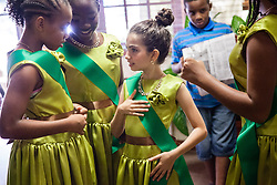 """All Saints dancers get dressed before the competition.  Dancing Classrooms Virgin Islands students compete in """"Colors of the Rainbow"""" team match competition at Reichhold Center for the Arts.  St. Thomas, USVI.  9 May 2015.  © Aisha-Zakiya Boyd"""