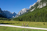 Mountain bikers explore Krma Valley, Triglavski narodni park, near Mojstrana, Slovenia, Europe. Glacially-carved Krma Valley, extends from Mojstrana village to Mount Triglav, in Triglavski narodni park, Slovenia's only national park. In Krma Valley, hike 5-6 hours/6.3miles one way on a non-technical former packhorse hut-supply route (now supplied by helicopter) from trailhead at 950m to scenic Dom Valentina Stanica / Stanicev Dom hut (2332 meters elevation), 20 km round trip, gaining 4658 feet/1420 meters, or a bit further to spectacular Kredarica Hut (aka Triglav hut / Triglavski dom na Kredarici, Slovenia's highest hut, 2515 meters). Reservations are highly recommended. Hike to Kredarica Hut via Konjsko Sedlo pass from Krma valley 6 hrs one way, non-technical, 1650m gain, well marked with red signs. Ascent of Mount Triglav is non-technical, but is not recommended for those who fear heights: 1.5 hours up from Kredarica (contrary to 1-hour sign, due to waiting for descenders) and 1 hour back. Or stay in scenic Planika hut, 2401m. In 1991, Slovenia declared full sovereignty from Yugoslavia. 80% of its 2 million people speak Slovene. In 2004, Slovenia joined NATO and the EU (European Union), and later adopted the Euro € currency. Slovenia is the richest Slavic nation per capita.