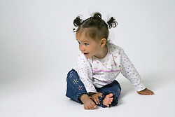 Baby learning to crawl on the floor,