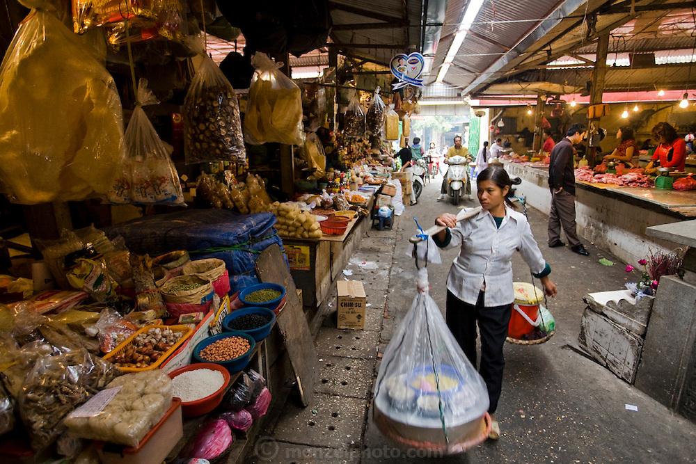 A street vendor carries her merchandise at Cho Chau Long Market in Hanoi, Vietnam.