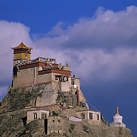 A Tibetan Buddhist monk stands on the roof of fortress-like Yumbu Lakang, the oldest castle  in Tibet, atop a hill near Tsedang.