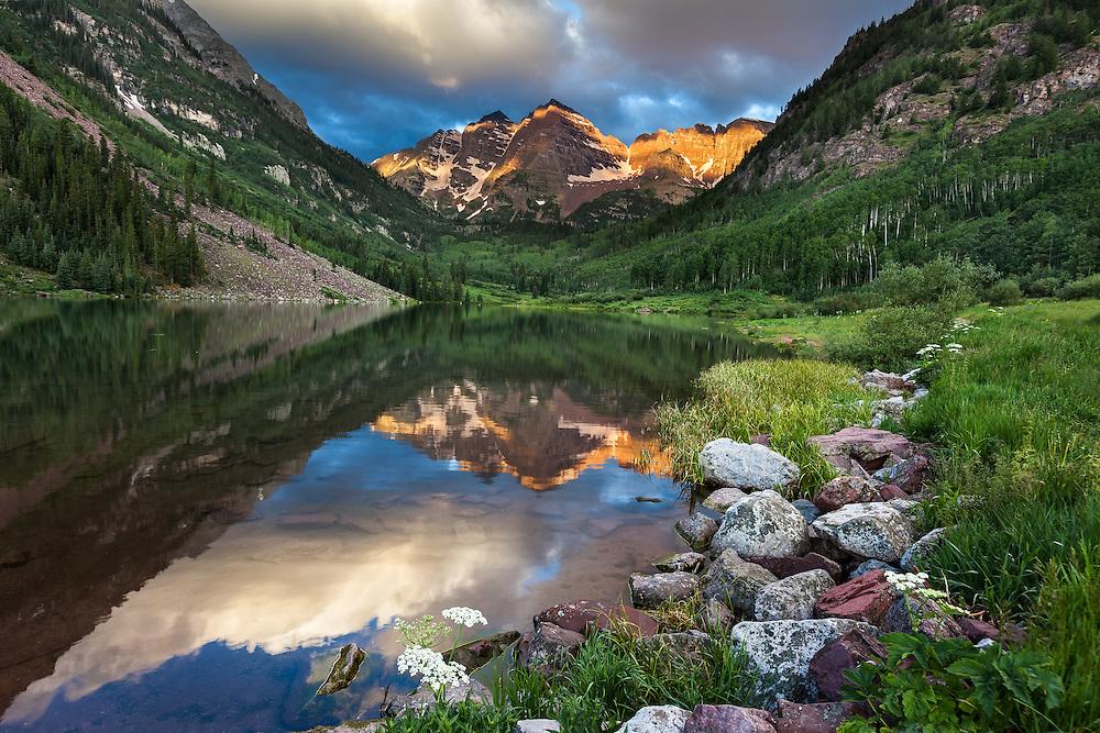 The still waters of Maroon Lake reflect Maroon Peak and North Maroon Peak (called the Maroon Bells) at sunrise in summer near Aspen, Colorado.