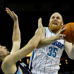 December 21, 2011; New Orleans, LA, USA; New Orleans Hornets center Chris Kaman (35) collides with Memphis Grizzlies small forward Josh Davis (18) as he shoots during the first quarter of a game at the New Orleans Arena.   Mandatory Credit: Derick E. Hingle-US PRESSWIRE