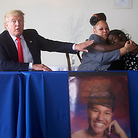 PHILADELPHIA, PA - September 2, 2016.  Republican Presidential nominee Donald J. Trump touches Shalga Hightower, 55, hugging her daughter, Jasmine Hightower, 26, with a photograph of another daughter, Iofemi Hightower, who was killed in 2007, at Greater Exodus Baptist Church in Philadelphia, PA on September 2, 2016.  CREDIT: Mark Makela for The New York Times