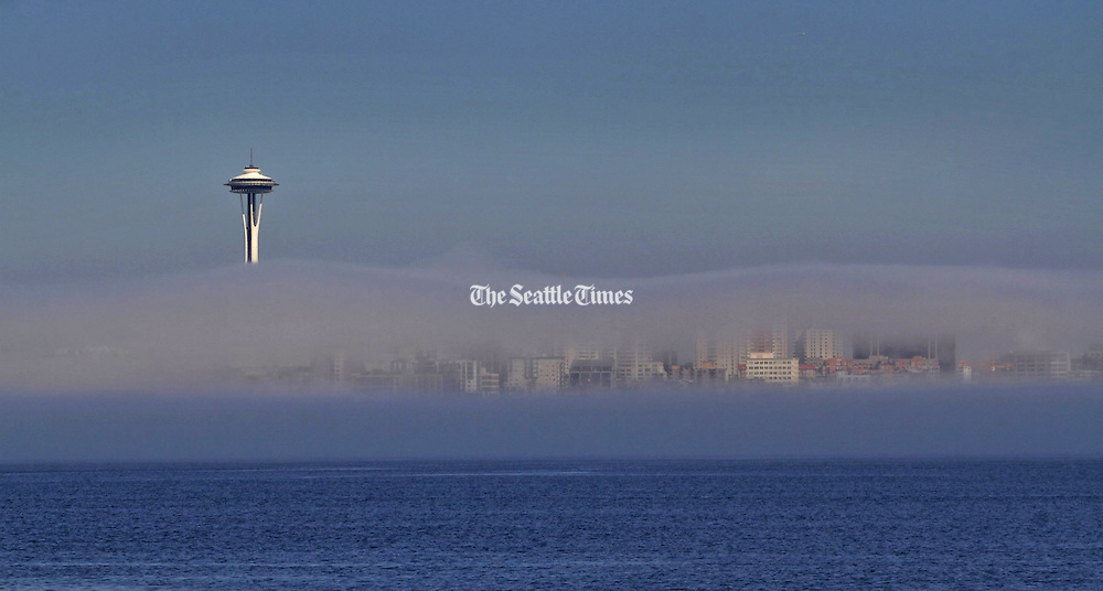 Part of the Seattle skyline and the Space Needle can be seen through the fog. (Ellen M. Banner / The Seattle Times)