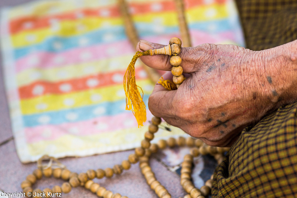15 JUNE 2013 - YANGON, MYANMAR: A man prays with prayer beads at Shwedagon Pagoda. The Shwedagon Pagoda is officially known as Shwedagon Zedi Daw and is also called the Great Dagon Pagoda or the Golden Pagoda. It is a 99 metres (325ft) tall pagoda and stupa located in Yangon, Burma. The pagoda lies to the west of on Singuttara Hill, and dominates the skyline of the city. It is the most sacred Buddhist pagoda in Myanmar and contains relics of the past four Buddhas enshrined: the staff of Kakusandha, the water filter of Koṇāgamana, a piece of the robe of Kassapa and eight strands of hair fromGautama, the historical Buddha. The pagoda was built between the 6th and 10th centuries by the Mon people, who used to dominate the area around what is now Yangon (Rangoon). The pagoda has been renovated numerous times through the centuries. Millions of Burmese and tens of thousands of tourists visit the pagoda every year, which is the most visited site in Yangon.  PHOTO BY JACK KURTZ