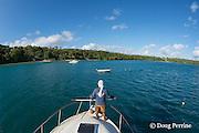 deck hand Patrick Atu prepares to pick up mooring line as charter fishing vessel Reel Addiction approaches its home base at Ika Lahi Fishing Lodge on Hunga Island, Vava'u, Kingdom of Tonga, South Pacific