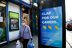 © Licensed to London News Pictures. 09/04/2020. London, UK. A woman wearing a face mask walks past a billboard in north London, which says 'CLAP FOR OUR CARERS' during the outbreak of the COVID-19 virus. Photo credit: Dinendra Haria/LNP