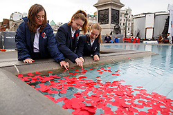 © Licensed to London News Pictures. 11/11/2014. LONDON, UK. Students of Eltham Hil School throw remembrance poppies to the fountains in Trafalgar Square during Silence in the Square event as part of Remembrance Day on Tuesday 11 November 2014. Photo credit : Tolga Akmen/LNP