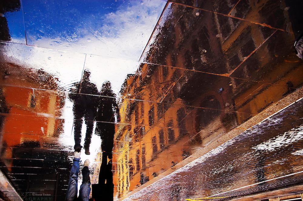 Reflection off a couple walking on a slate sidewalk in Rome Italy. -via del babuino