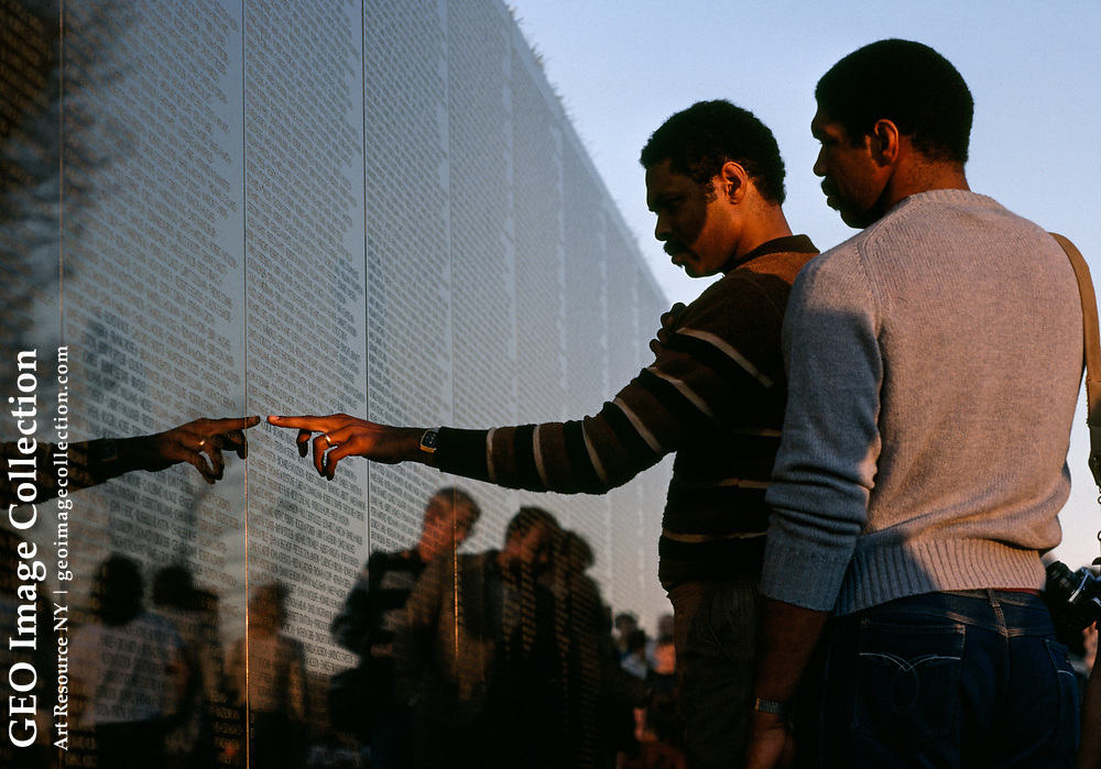 African American man pointing to a name on the Vietnam Veterans Memorial.