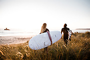 Surfers walking through a grass path on the sand dunes, ready to go surfing at Le Braye, St Ouen's Bay, Jersey with views out to La Rocco Tower in the water