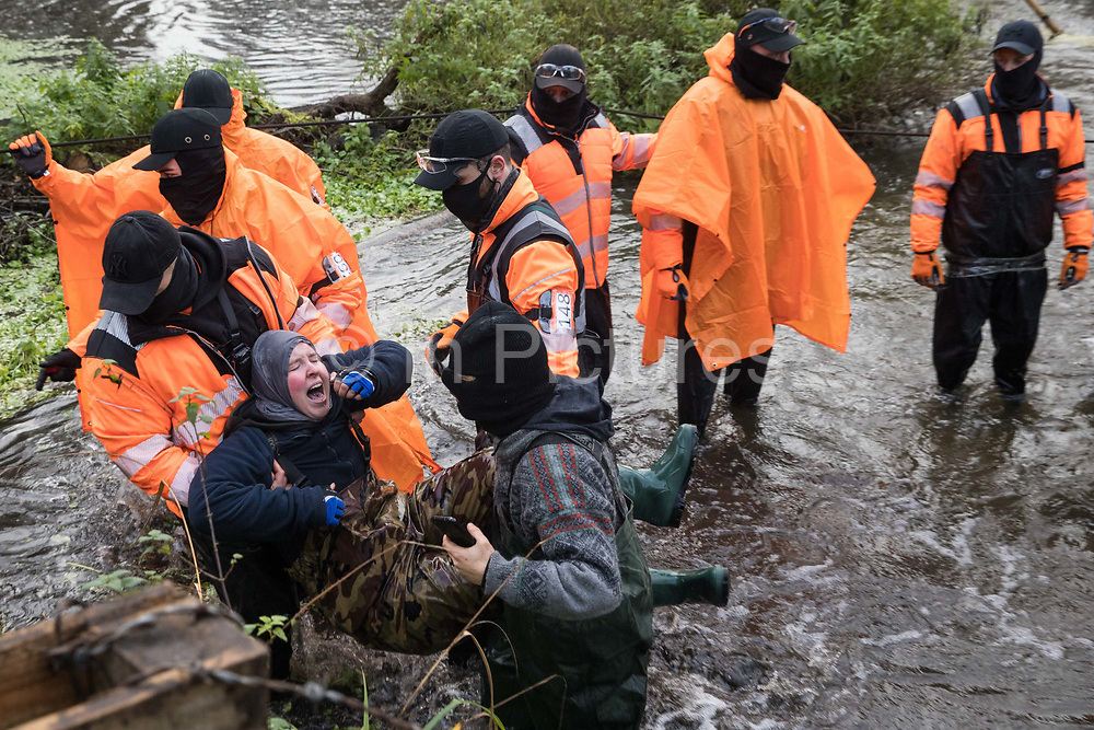 A distressed anti-HS2 activist is removed from the river Colne by security guards and a fellow activist on 8th December 2020 in Denham, United Kingdom. The activists had been supporting Dan Hooper, widely known as Swampy during the 1990s, who had occupied a bamboo tripod positioned in the river the previous day in order to delay the building of a bridge as part of works for the controversial HS2 high-speed rail link and a large security operation involving officers from at least three police forces, the National Eviction Team and HS2 security guards was put in place to facilitate his removal.