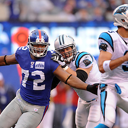 Defensive end Osi Umenyiora #72 of the New York Giants rushes quarterback Matt Moore #3 of the Carolina Panthers during second half NFL action in the New York Giants' 31-18 victory over the Carolina Panthers at New Meadowlands Stadium in East Rutherford, New Jersey.