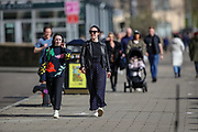 People walk by the city centre's river Tyne in Newcastle on Tuesday, March 16, 2021. Spanning the Tyne, modern Gateshead Millennium Bridge, noted for its unique tilting aperture, which is a symbol of the 2 cities. (Photo/ Vudi Xhymshiti)