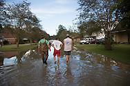 Forrest Bellue,,Victoria Ardoin and Cameron DeBate walk through a flooded neighborhood in Denham Springs Louisiana after a record flood.