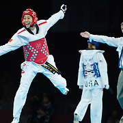 Yuzhuo Hou of China reacted to her 1-0 sudden death victory over Diana Lopez of the United States, right, as referee David Coupar signaled the end of the match in women's 57kg action at the ExCeL centre during the 2012 Summer Olympic Games in London, England, Thursday, August 9, 2012. (David Eulitt/Kansas City Star/MCT)