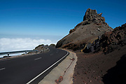 Road to nowhere passing through red volcanic rock formations in the Caldera de Taburiente National Park in La Palma, Canary Islands, Spain. La Palma, also San Miguel de La Palma, is the most north-westerly Canary Island in Spain. La Palma has an area of 706 km2 making it the fifth largest of the seven main Canary Islands. Caldera de Taburiente National Park Spanish: Parque Nacional de la Caldera de Taburiente is a national park on the island of La Palma, Canary Islands, Spain. It contains the enormous expanse of the Caldera de Taburiente, once believed to be a huge crater, but nowadays known to be a mountain arch with a curious crater shape, which dominates the northern part of the island. It was designated as a national park in 1954. The caldera is about 10 km across, and in places the walls tower 2000 m over the caldera floor.