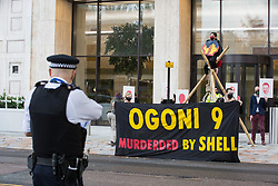 London, UK. 10 November, 2020. A Metropolitan Police officer observes environmental activists from Extinction Rebellion protesting outside the Shell Centre on the 25th anniversary of the killings of the Ogoni Nine. The Ogoni Nine, leaders of the Movement for the Survival of the Ogoni People (MOSOP), were executed by the Nigerian government in 1995 after having led a series of peaceful marches involving an estimated 300,000 Ogoni people against the environmental degradation of the land and waters of Ogoniland by Shell and to demand both a share of oil revenue and greater political autonomy.
