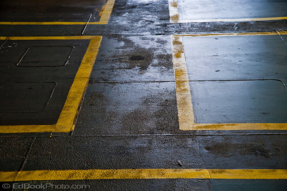 Walkways on a Washington State Ferry car deck show wear, oil spots, and rust in a graphic abstract photograph.