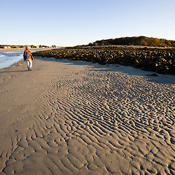 A man walks at low tide at the outlet of the Little River in Biddeford, Maine. Timber Point.