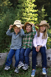 three children in cowboy hats and jeans outdoors in Montana