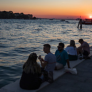 People gather along the Grand Canal in Venice, Italy to sip wine and watch the sunset.