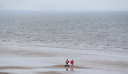 Two people dry off after a dip in the North sea today in the pouring rain in Saltburn in North Yorkshire.